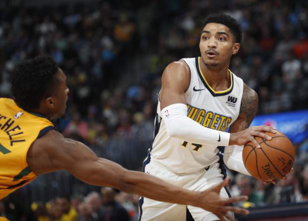 Denver Nuggets guard Gary Harris, right, looks to pass the ball as Utah Jazz guard Donovan Mitchell defends in the first half of an NBA basketball game, Tuesday, Dec. 26, 2017, in Denver. (AP Photo/David Zalubowski)