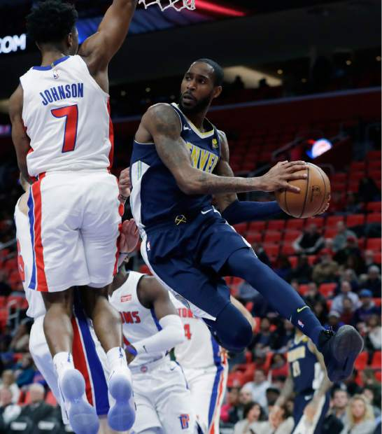 Denver Nuggets guard Will Barton, right, passes around Detroit Pistons forward Stanley Johnson, left, during the second half of an NBA basketball game, Tuesday, Dec. 12, 2017, in Detroit. (AP Photo/Carlos Osorio)