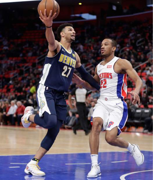 Denver Nuggets guard Jamal Murray (27) shoots as Detroit Pistons guard Avery Bradley (22) closes in during the second half of an NBA basketball game, Tuesday, Dec. 12, 2017, in Detroit. (AP Photo/Carlos Osorio)