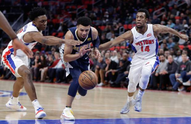 Denver Nuggets guard Jamal Murray, center, dribbles between Detroit Pistons forward Stanley Johnson, left, and guard Ish Smith, right, during the second half of an NBA basketball game, Tuesday, Dec. 12, 2017, in Detroit. (AP Photo/Carlos Osorio)