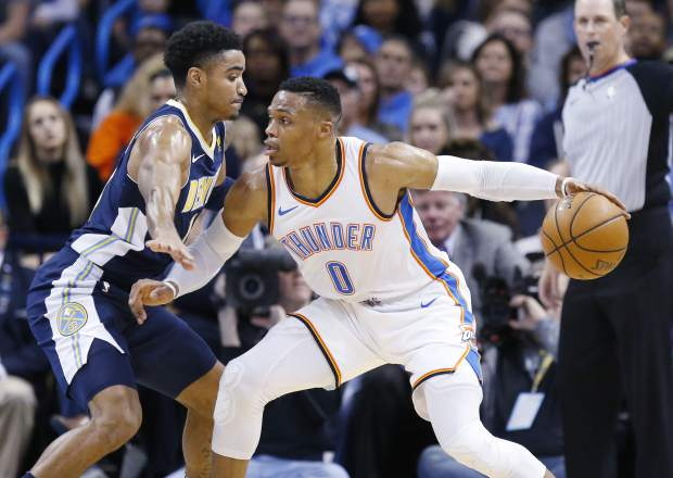 Oklahoma City Thunder guard Russell Westbrook (0) drives against Denver Nuggets guard Gary Harris, left, in the first quarter of an NBA basketball game in Oklahoma City, Monday, Dec. 18, 2017. (AP Photo/Sue Ogrocki)