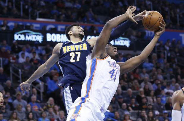Denver Nuggets guard Jamal Murray (27) and Oklahoma City Thunder center Dakari Johnson (44) reach for a rebound in the second quarter of an NBA basketball game in Oklahoma City, Monday, Dec. 18, 2017. (AP Photo/Sue Ogrocki)