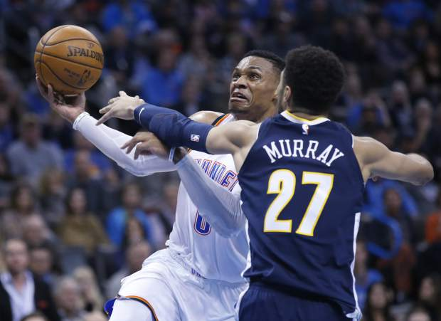Oklahoma City Thunder guard Russell Westbrook (0) drives to the basket past Denver Nuggets guard Jamal Murray (27) in the fourth quarter of an NBA basketball game in Oklahoma City, Monday, Dec. 18, 2017. (AP Photo/Sue Ogrocki)