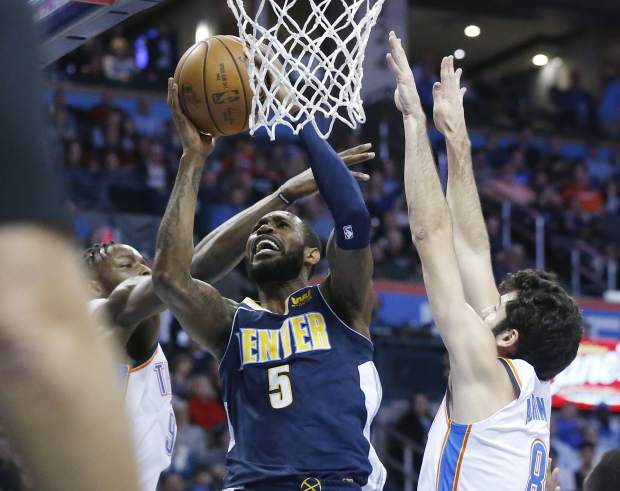 Denver Nuggets guard Will Barton (5) shoots between Oklahoma City Thunder forward Jerami Grant, left, and guard Alex Abrines, right, in the first quarter of an NBA basketball game in Oklahoma City, Monday, Dec. 18, 2017. (AP Photo/Sue Ogrocki)