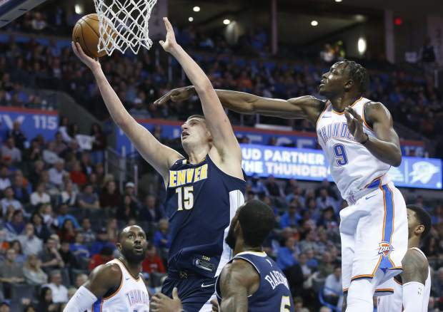 Denver Nuggets center Nikola Jokic (15) shoots in front of Oklahoma City Thunder forward Jerami Grant (9) in the second quarter of an NBA basketball game in Oklahoma City, Monday, Dec. 18, 2017. (AP Photo/Sue Ogrocki)