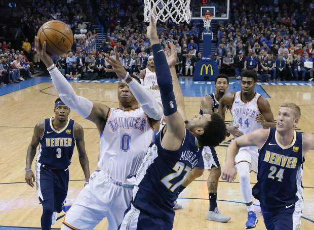 Oklahoma City Thunder guard Russell Westbrook (0) shoots as Denver Nuggets guard Jamal Murray (27) defends in the first quarter of an NBA basketball game in Oklahoma City, Monday, Dec. 18, 2017. (AP Photo/Sue Ogrocki)