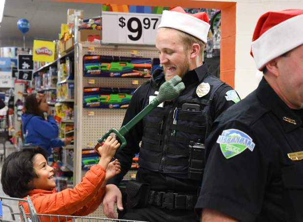 Carbondale officer Brandyn Rupp plays with six-year-old Maxi Pacheco while they wait in line to checkout at Walmart during the annual Shop With a Cop on Saturday morning.
