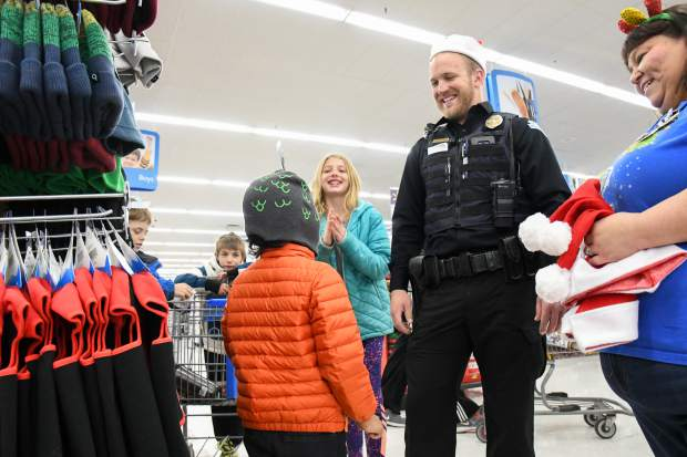 Carbondale Officer Brandyn Rupp helps 6-year-old Maxi Pacheco pick out a new winter hat during the annual Shop With a Cop on Saturday afternoon.