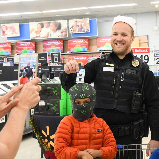 Carbondale officer Brandyn Rupp gets his photo taken with 6-year-old Maxi Pacheco during the annual Shop With a Cop on Saturday afternoon.