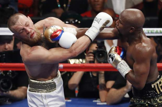 FILE - In this Aug. 26, 2017, file photo, Floyd Mayweather Jr., right, hits Conor McGregor during a super welterweight boxing match in Las Vegas. (AP Photo/Eric Jamison, File)