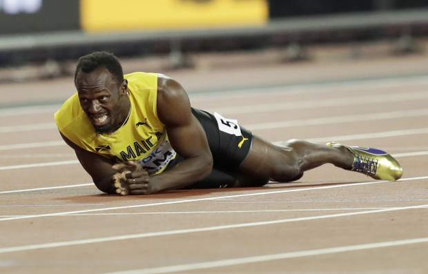 FILE - In this Aug. 12, 2017, file photo, Jamaica's Usain Bolt lies on the track after he injured himself in the 4x100 meter relay final at the World Athletics Championships in London. (AP Photo/Tim Ireland, File)