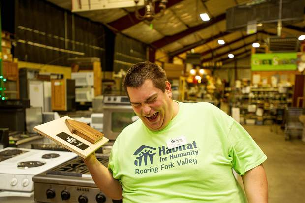 Habitat for Humanity employee Brian Wilson laughs while bantering with a coworker at the downvalley ReStore on Wednesday. Wilson received a plaque acknowledging him as