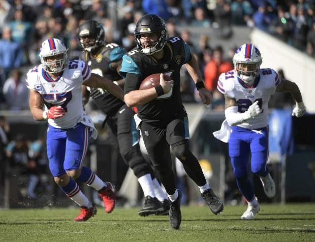 Jacksonville Jaguars quarterback Blake Bortles (5) rushes for yardage past Buffalo Bills outside linebacker Lorenzo Alexander (57) and free safety Jordan Poyer (21) in the first half of an NFL wild-card playoff football game, Sunday, Jan. 7, 2018, in Jacksonville, Fla. (AP Photo/Phelan M. Ebenhack)