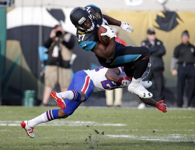 Jacksonville Jaguars running back Leonard Fournette (27) makes a reception over Buffalo Bills defensive back Leonard Johnson in the second half of an NFL wild-card playoff football game, Sunday, Jan. 7, 2018, in Jacksonville, Fla. (AP Photo/Stephen B. Morton)