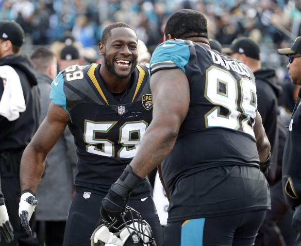 Jacksonville Jaguars defensive end Carroll Phillips (59) and defensive tackle Marcell Dareus (99) celebrate during the final moments of an NFL wild-card playoff football game against the Buffalo Bills, Sunday, Jan. 7, 2018, in Jacksonville, Fla. (AP Photo/Stephen B. Morton)
