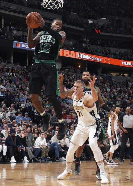 Boston Celtics guard Terry Rozier, front, pulls down a rebound in front of Denver Nuggets center Mason Plumlee, center, and Celtics forward Marcus Morris in the first half of an NBA basketball game Monday, Jan. 29, 2018, in Denver. (AP Photo/David Zalubowski)