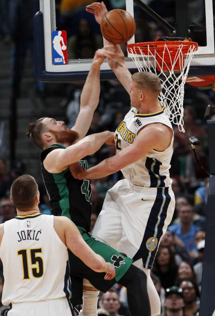 Denver Nuggets center Mason Plumlee, right, goes up to block a shot by Boston Celtics center Aron Baynes in the first half of an NBA basketball game Monday, Jan. 29, 2018, in Denver. (AP Photo/David Zalubowski)