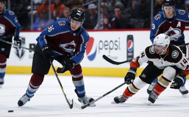 Colorado Avalanche right wing Mikko Rantanen, left, of Finland, loses control of the puck as Anaheim Ducks center Adam Henrique defends in the third period of an NHL hockey game Monday, Jan. 15, 2018, in Denver. The Avalanche won 3-1. (AP Photo/David Zalubowski)