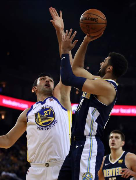 Denver Nuggets' Jamal Murray, right, shoots against Golden State Warriors' Zaza Pachulia (27) during the first half of an NBA basketball game Monday, Jan. 8, 2018, in Oakland, Calif. (AP Photo/Ben Margot)