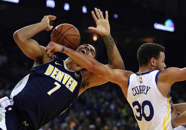 Denver Nuggets' Trey Lyles, left, is fouled by Golden State Warriors' Stephen Curry (30) during the first half of an NBA basketball game Monday, Jan. 8, 2018, in Oakland, Calif. (AP Photo/Ben Margot)