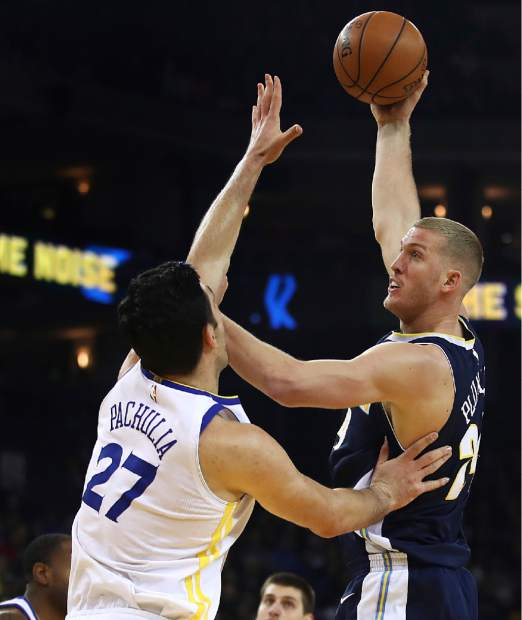 Denver Nuggets' Mason Plumlee, right, shoots over Golden State Warriors' Zaza Pachulia (27) during the first half of an NBA basketball game Monday, Jan. 8, 2018, in Oakland, Calif. (AP Photo/Ben Margot)