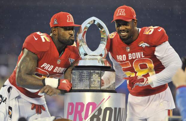 AFC linebacker Von Miller (58), of the Denver Broncos and tight end Delanie Walker (82), of the Tennessee Titans, pose with the NFL Pro Bowl trophy after defeating the AFC 24-23, in Orlando, Fla., Sunday, Jan. 28, 2018. (AP Photo/Steve Nesius)