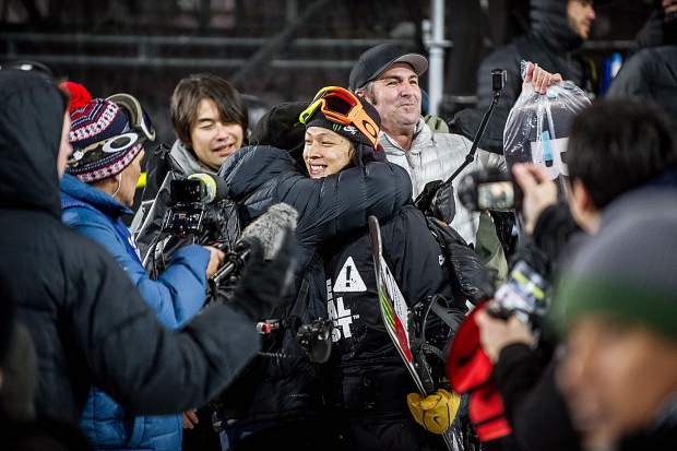 Ayumu Hirano of Japan gets hugged by Oakley staff member Masa Tanaka after winning the finals for the superpipe snowboard finals on Sunday. Hirano nearly received a perfect score and claimed gold with a 99.