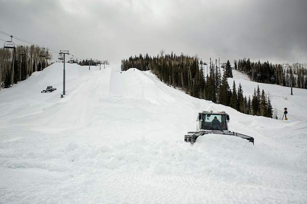 A snowcat driven by Snowmass terrain park manager Yannick Rioux pushes snow on Saturday below the U.S. Grand Prix superpipe and slopestyle course for the upcoming event this week.