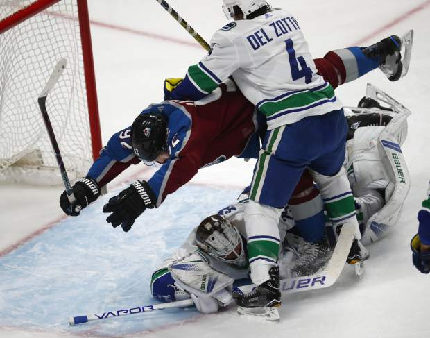 Colorado Avalanche left wing Gabriel Landeskog, left, flies over Vancouver Canucks goaltender Jacob Markstrom, right bottom, after being hit by defenseman Michael Del Zotto, right, in the first period of an NHL hockey game Monday, Feb. 26, 2018, in Denver. (AP Photo/David Zalubowski)