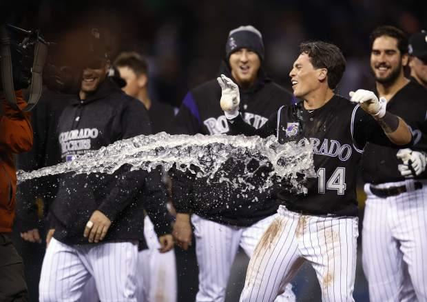 Colorado Rockies' Tony Wolters (14) is hit by a stream of water as players celebrate after Wolters drew a bases-loaded walk off Atlanta Braves relief pitcher Arodys Vizcaino to force in the winning run in the 10th inning of a baseball game Saturday, April 7, 2018, in Denver. Colorado won 3-2. (AP Photo/David Zalubowski)
