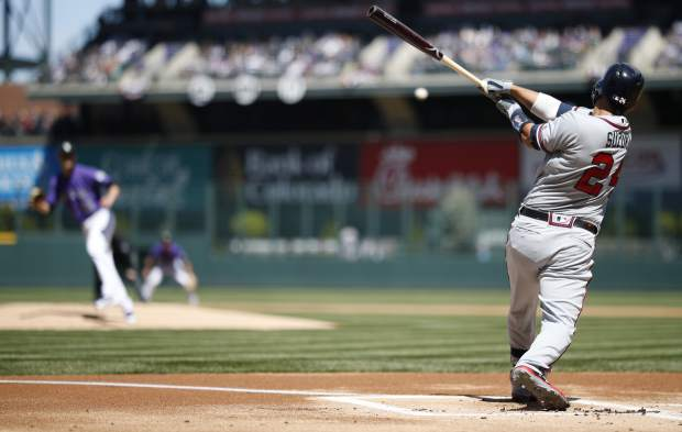 Atlanta Braves' Kurt Suzuki, front, lines out on a pitch from Colorado Rockies starting pitcher Kyle Freeland to end the top of the first inning of a baseball game Sunday, April 8, 2018, in Denver. (AP Photo/David Zalubowski)