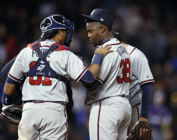 Atlanta Braves catcher Carlos Perez, left, confers with relief pitcher Arodys Vizcaino, how had loaded the bases by walking Colorado Rockies' Trevor Story in the 10th inning of a baseball game Saturday, April 7, 2018, in Denver. Vizcaino walked Tony Wolters on four pitches to allow in the winning run. Colorado won 3-2. (AP Photo/David Zalubowski)
