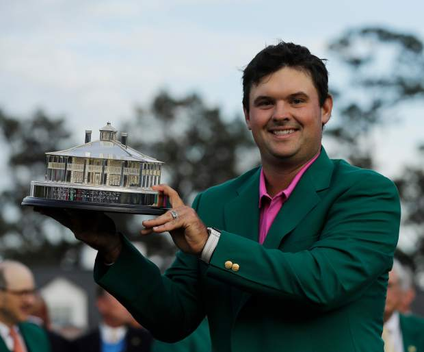 Patrick Reed holds the championship trophy after winning the Masters golf tournament Sunday, April 8, 2018, in Augusta, Ga. (AP Photo/David J. Phillip)