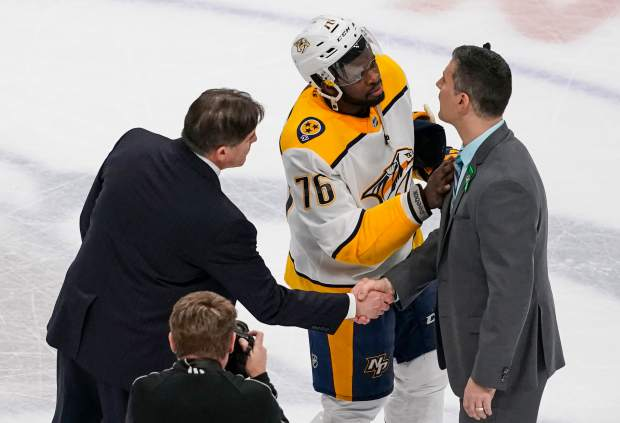 Nashville Predators head coach Peter Laviolette, left, shakes hands with Colorado Avalanche head coach Jared Bednar while Predators defenseman P.K. Subban (76) talks following Game 6 of an NHL hockey first-round playoff series Sunday, April 22, 2018, in Denver. Nashville beat Colorado 5-0 to win the series. (AP Photo/Jack Dempsey)