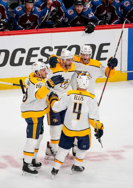 Nashville Predators defenseman Mattias Ekholm (14) is congratulated by teammates Colton Sissons (10), Ryan Ellis (4) and Austin Watson (51) after scoring a goal against the Colorado Avalanche during the first period in Game 6 of an NHL hockey first-round playoff series Sunday, April 22, 2018, in Denver. (AP Photo/Jack Dempsey)