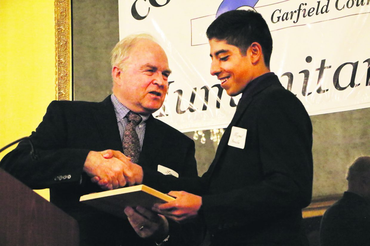 """Miguel Gonzalez, a senior at Rifle High School and volunteer for LIFT-UP and Grand River Health, accepts the """"Inspiring Youth"""" award from Garfield County Commissioner Tom Jankovsky at the Humanitarian Service Awards on Monday night in Glenwood Springs. """"His work ethic and leadership skills will take him far,"""" Jankovsky said of Gonzalez."""
