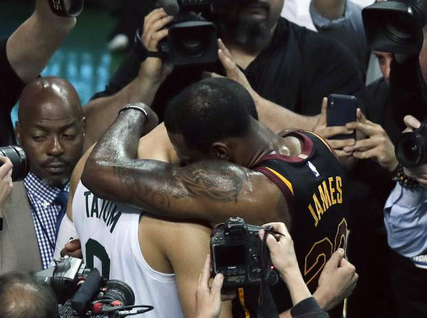 Cleveland Cavaliers forward LeBron James embraces Boston Celtics forward Jayson Tatum after the Cavaliers beat the Celtics 87-79 in Game 7 of the NBA basketball Eastern Conference finals, Sunday, May 27, 2018, in Boston. (AP Photo/Charles Krupa)