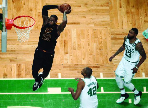 Cleveland Cavaliers forward LeBron James soars to dunk in front of Boston Celtics forward Al Horford (42) and forward Marcus Morris (13) during the first half in Game 7 of the NBA basketball Eastern Conference finals, Sunday, May 27, 2018, in Boston. (AP Photo/Charles Krupa)
