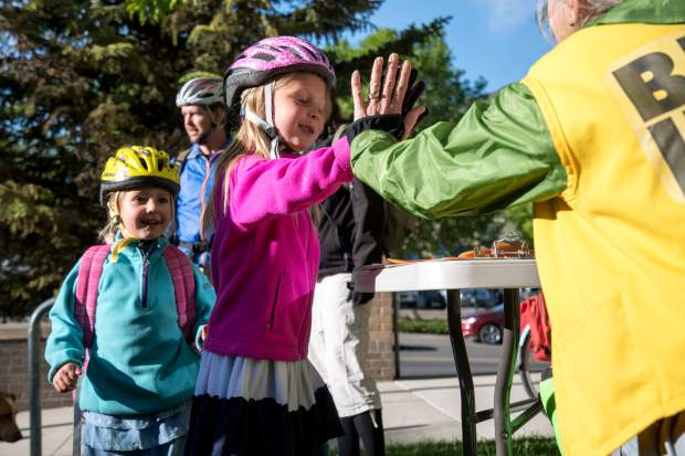 Six-year-old Norah Buirgy gets a high-five from a bike information volunteer on the front lawn of the Glenwood Springs City Hall on Friday, which was National Bike to Work Day.