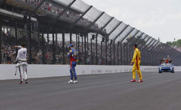 Graham Rahal, left, Alexander Rossi, center, and Ryan Hunter-Reay wait on the track to greet Will Power, of Australia, after Power won the Indianapolis 500 auto race at Indianapolis Motor Speedway in Indianapolis, Sunday, May 27, 2018. (AP Photo/AJ Mast)