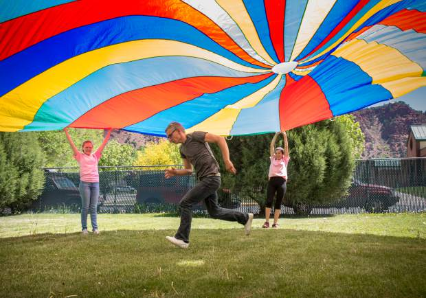 Mountain Valley Services client Dawson Wisdom runs underneath the parachute during a game on the lawn with Miss Strawberry Days contestants during Thursday's field day.