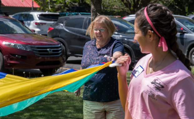 Mountain Valley Developmental Servies client Molly Murray plays a parachute game with other clients and Miss Strawberry Days contestants during Thursday's field day.