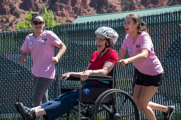 Miss Strawberry Days contestants Litzy Rivera and Brittany Rhodes push and encourage Mountain Valley Developmental Services client Patty Taylor through the obstacle course during Thursday's field day.