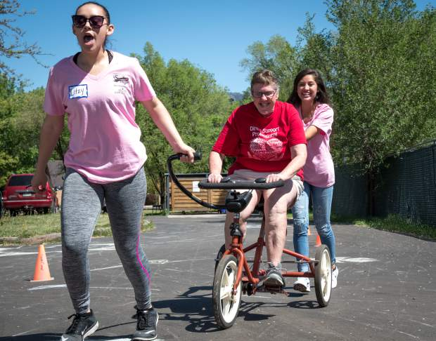 Miss Strawberry Days contestants Litzy Rivera and Leslia Serrano help Mountain Valley Developmental Services client Suzanne Simmons through the obstacle course during Thursday's field day.
