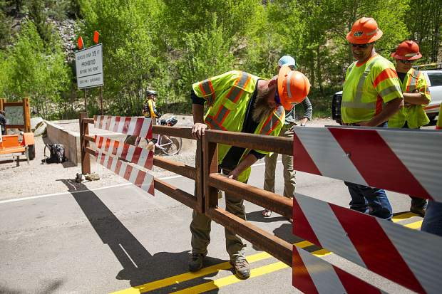 Colorado Department of Transportation worker Jonathan Arnold unlocks the gate on Independence Pass Road on Thursday at noon for car traffic for the summer season.