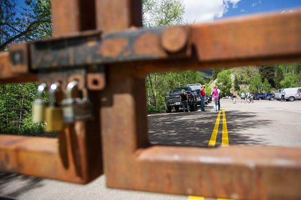 Cars and people line up at the Independence Pass gate in Aspen waiting for the Colorado Department of Transportation workers to come down and unlock it at noon on Thursday for the summer season. The first vehicle was a family from Ava, Missouri, Chad Emmerson his with Chantelle and son Craig, 2.
