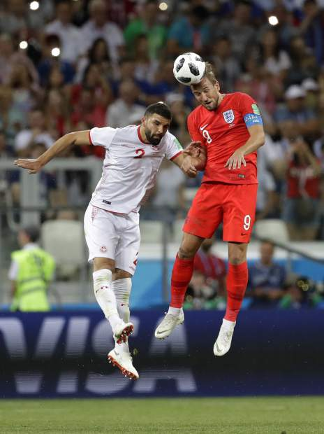 England's Harry Kane, right, and Tunisia's Syam Ben Youssef challenge for the ball during the group G match between Tunisia and England at the 2018 soccer World Cup in the Volgograd Arena in Volgograd, Russia, Monday, June 18, 2018. (AP Photo/Sergei Grits)