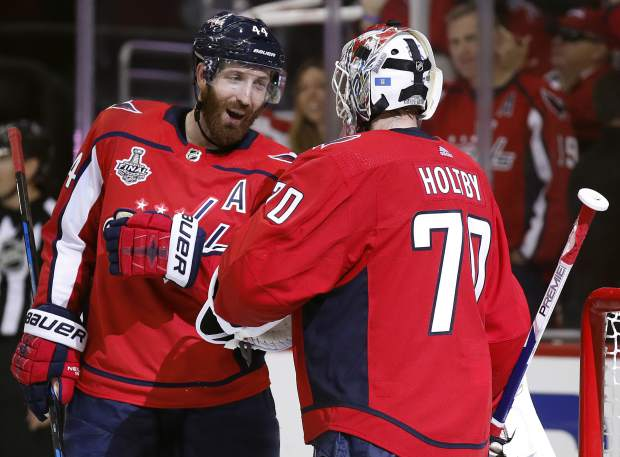 Washington Capitals defenseman Brooks Orpik, left, celebrates the team's 6-2 win over the Vegas Golden Knights with Washington Capitals goaltender Braden Holtby, right, in Game 4 of the NHL hockey Stanley Cup Final, Monday, June 4, 2018, in Washington. (AP Photo/Alex Brandon)