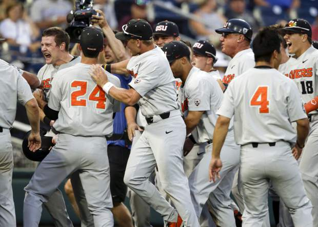Oregon State designated hitter Kyle Nobach. left, celebrates at the dugout after he hit a three-run home run in the seventh inning of an NCAA College World Series baseball elimination game against Washington in Omaha, Neb., Monday, June 18, 2018. Michael Gretler and Adley Rutschman also scored on the play as Oregon State won 14-5. (AP Photo/Nati Harnik)
