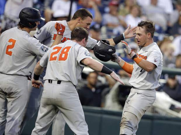 Oregon State's Tyler Malone, right, is greeted by Kyle Nobach (28) and Cadyn Grenier (2) after he hit a solo home run against Washington in the eighth inning of an NCAA College World Series baseball elimination game in Omaha, Neb., Monday, June 18, 2018. Oregon State won 14-5. (AP Photo/Nati Harnik)